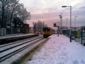 A snowy shot of Maghull Station with an Ormskirk bound train approaching