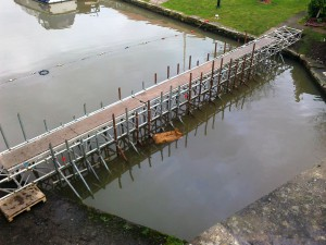 Temporary dams are being built either side of the bridge. When complete the water will be pumped out to allow further repair work.
