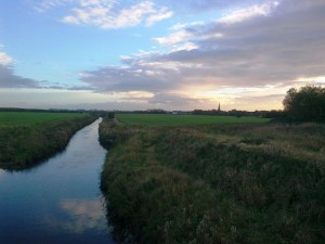 This shot, with Sefton Church in the background, is looking south down the River Alt (it flows north) towards Bridges Lane. Dovers Brook joins at this point on the left of the photo. St Helen's Gutter joins on the right but you can hardly see it due to the tall bunds.