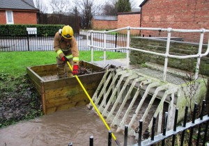 Hall Lane, Maghull with a Merseyside Fire & Rescue worker clearing debris from Whinney Brook.