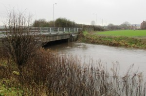 A swollen River Alt as it just about manages to duck under Bridges Lane near Sefton Village.